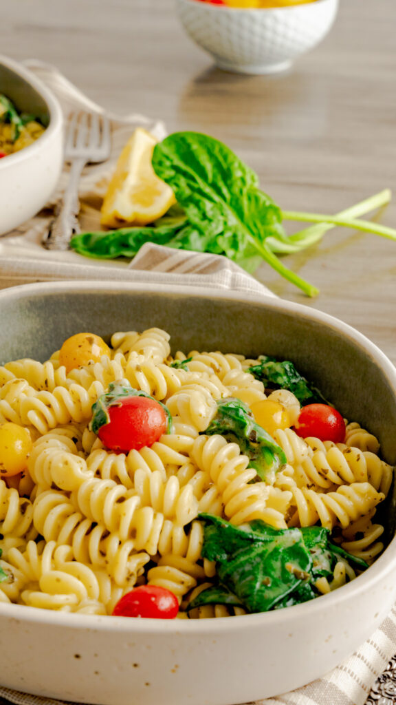 Side view of rotini pasta with cherry tomatoes and spinach.