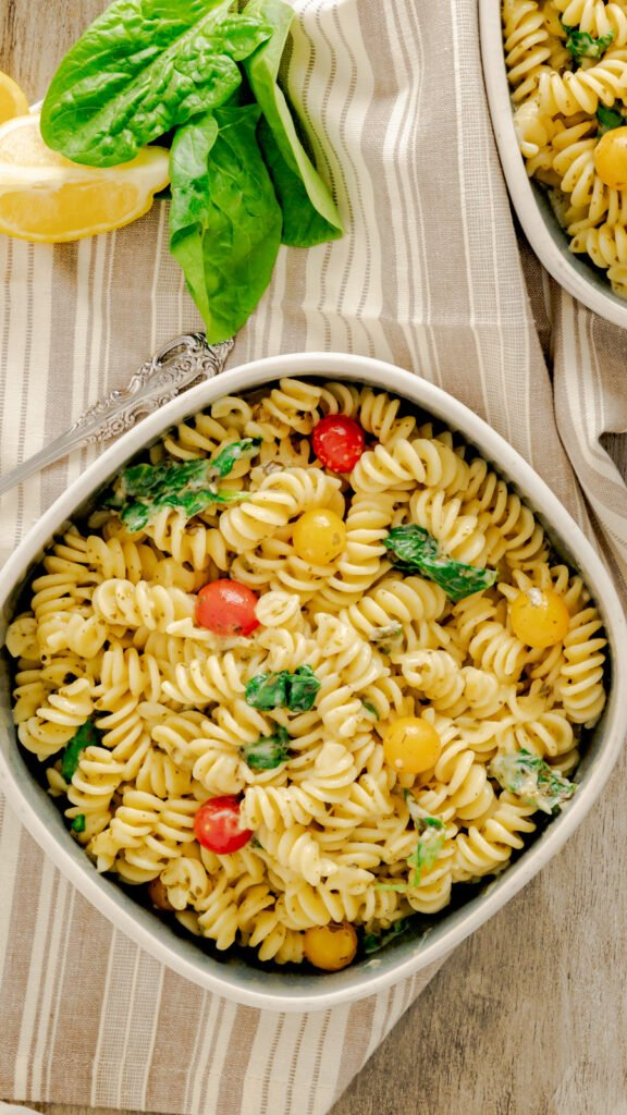 One bowl of instant pot pesto pasta tossed with Parmesan and cherry tomatoes.