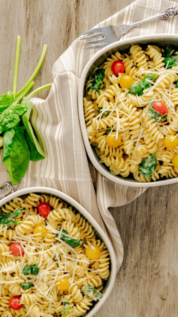Two bowls of pesto pasta topped with Parmesan and cherry tomatoes.