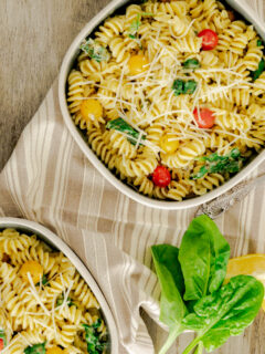 two bowls of pesto pasta topped with Parmesan and cherry tomatoes