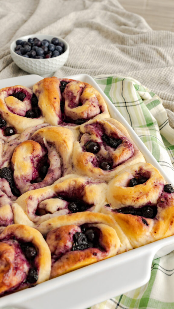 Unglazed sweet rolls with cooking blueberries oozing out of the top.
