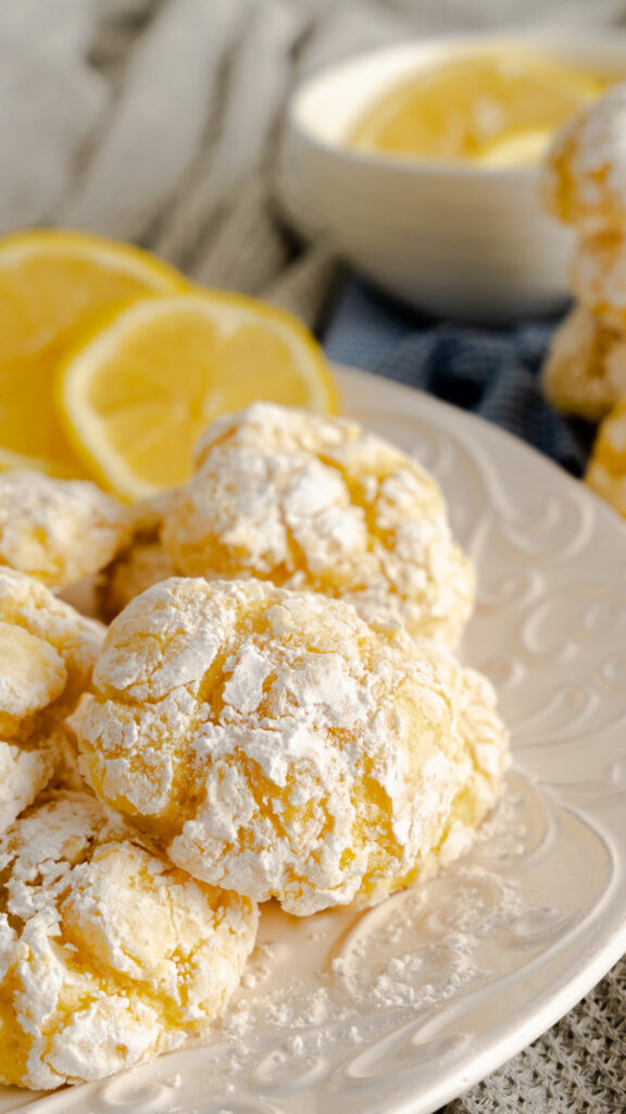 Decorative plate of powdered lemon cookies and sliced lemons.