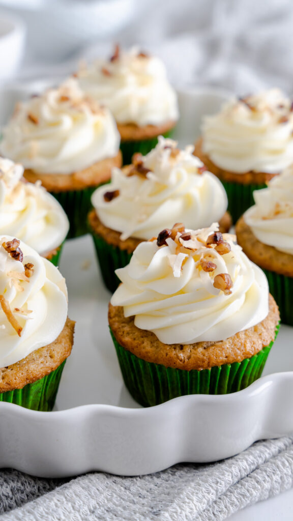 Hummingbird cupcakes topped with pineapple cream cheese frosting and garnished with pecans and coconut.