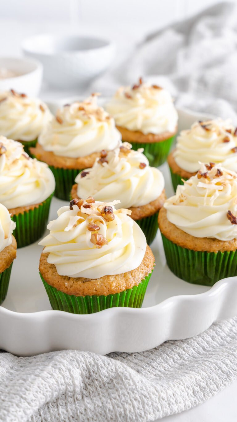 Hummingbird Cake cupcakes in green wrappers and topped with a cream cheese frosting with toasted pecans and coconut.