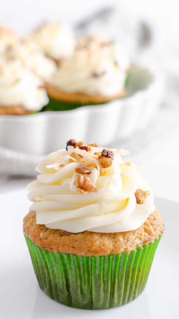 One hummingbird cake cupcake in a green cupcake wrapper topped with toasted pecans and coconut.