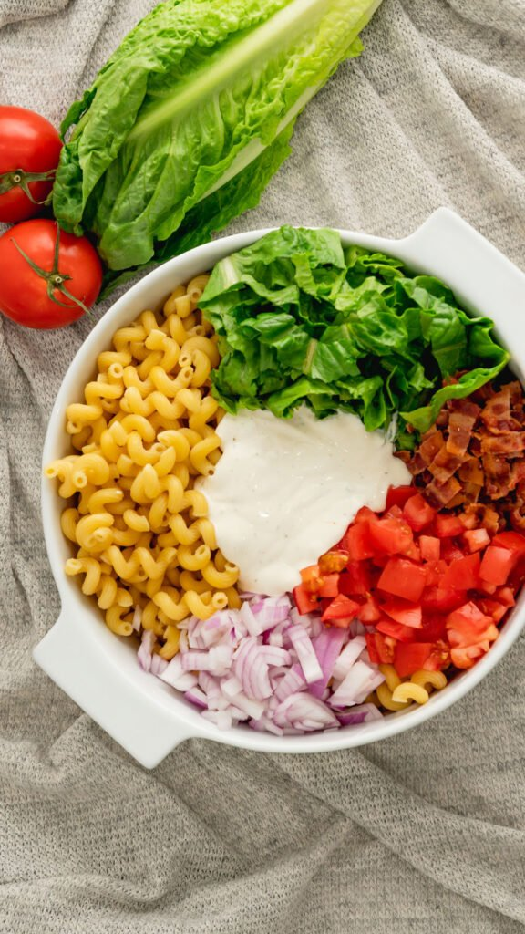 Unmixed ingredients for the Instant Pot BLT Pasta salad in a white casserole dish.
