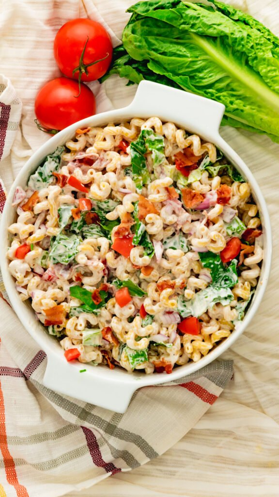 Top view of BLT pasta salad made with cavatappi pasta in white casserole dish.