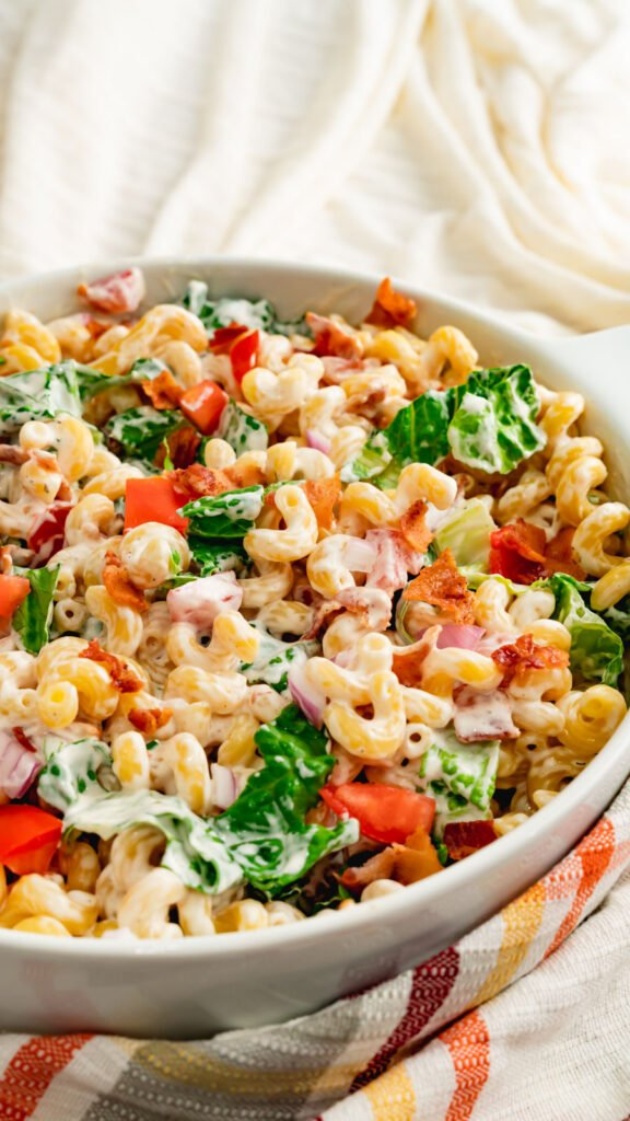 A white casserole dish with pasta, chopped bacon, chopped romaine, and ranch dressing.