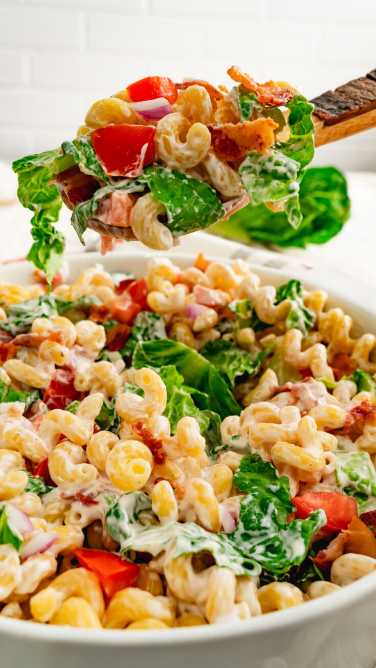 A large serving spoonful of BLT Pasta salad with lettuce, tomatoes, pasta, and bacon.