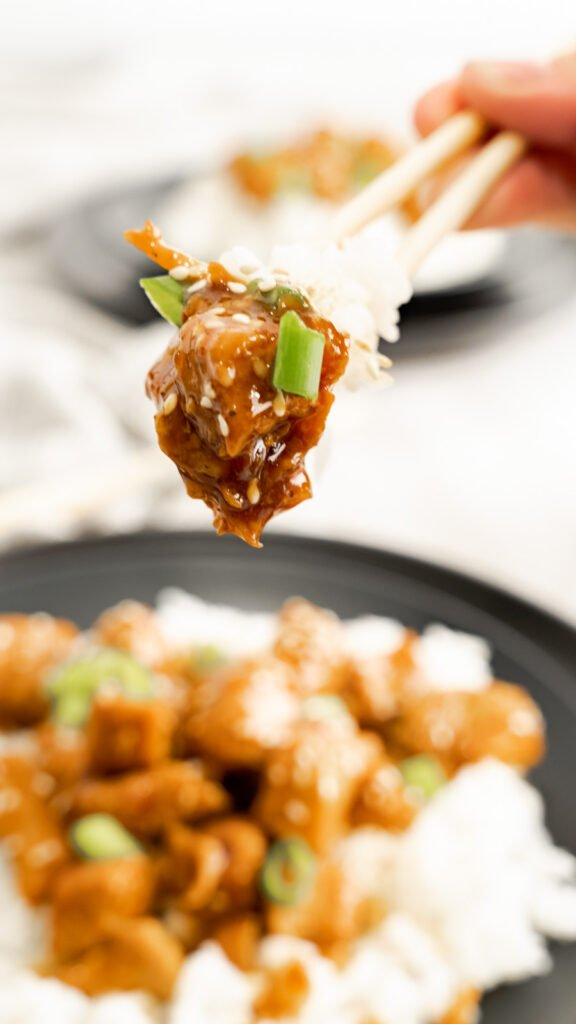 A hand holding chopsticks up with jasmine rice and honey sesame chicken above a black plate of chicken and rice.