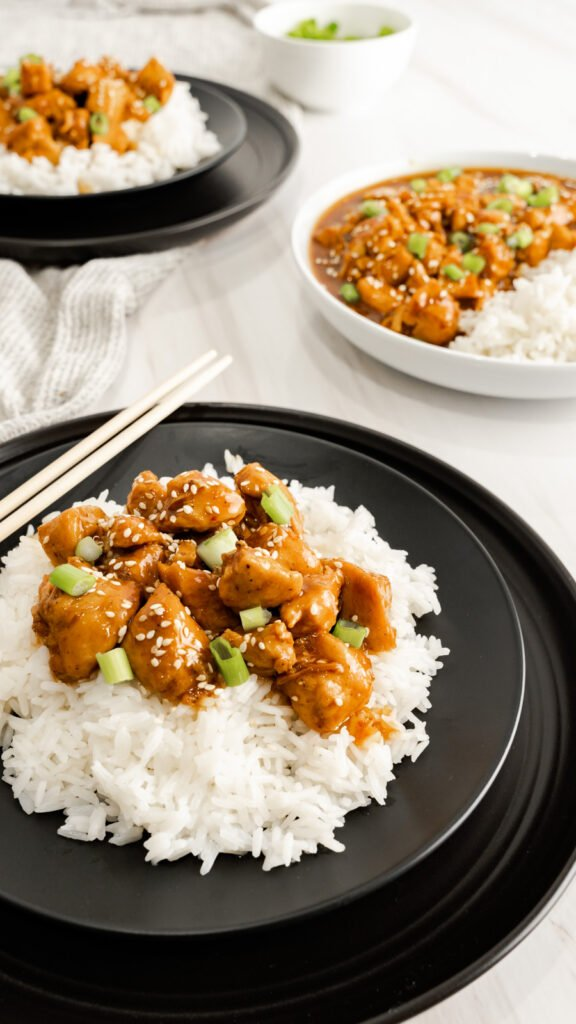 Chopsticks propped on black plate with white rice and honey sesame chicken