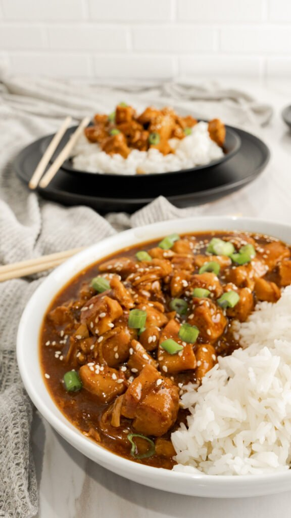 Instant Pot Honey Sesame Chicken garnished with sesame seeds and scallions on one side of a white bowl and Instant Pot rice served on the other side of the bowl.