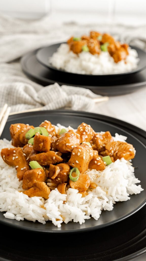 Close up of black plate with a bed or jasmine rice topped with honey sesame chicken.