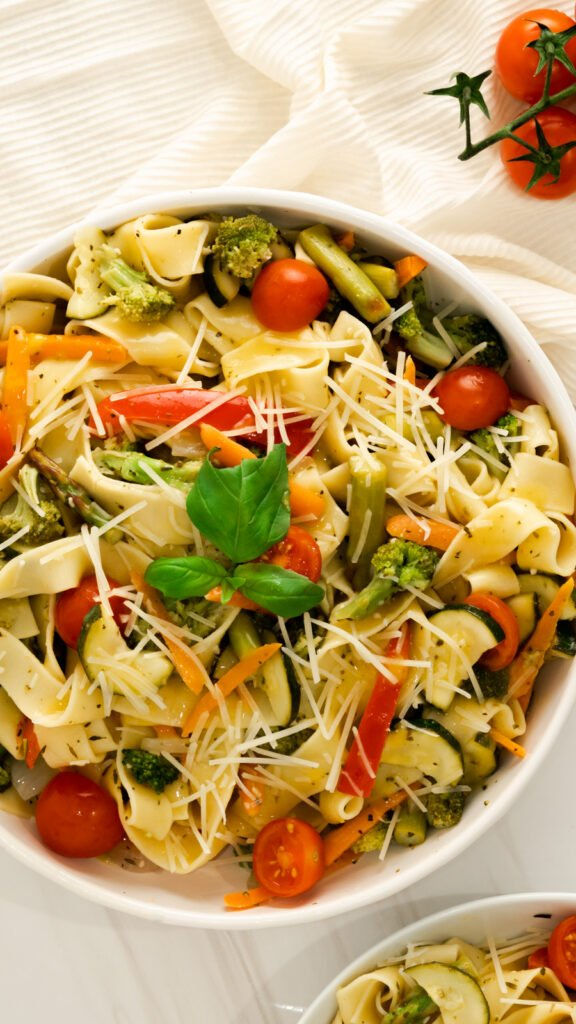 A large bowl of Instant Pot Pasta Primavera with fresh basil, parmesan, and halved cherry tomatoes.