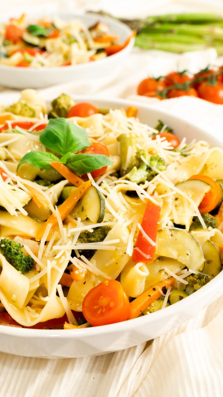 A large bowl of pasta primavera with parmesan and lemon garlic butter sauce