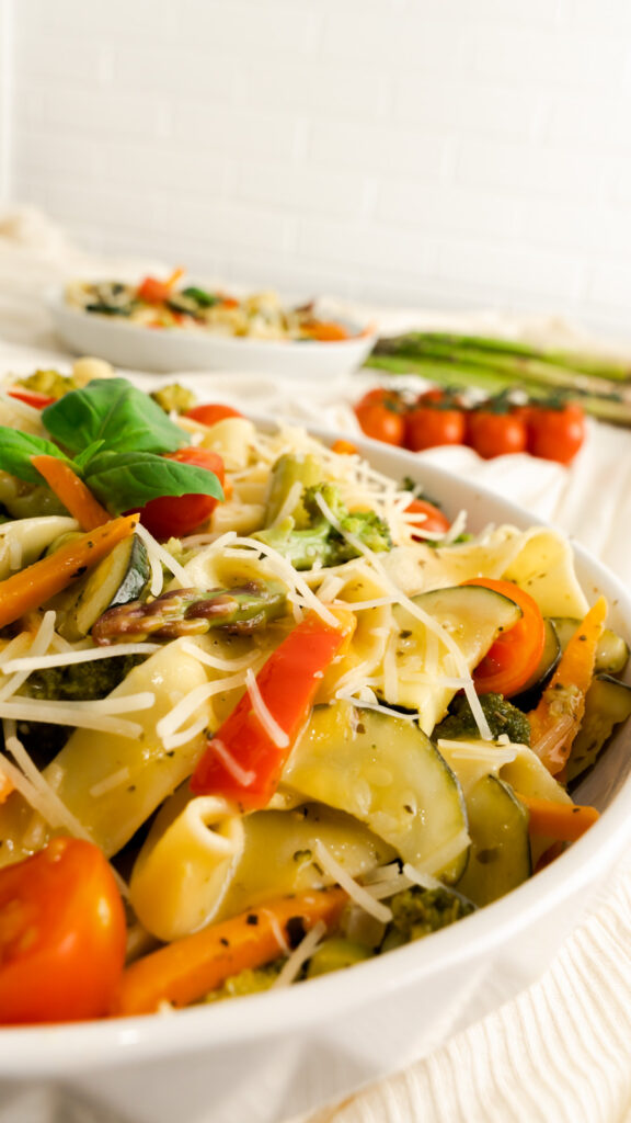 Side view of primavera pasta salad in white swerving bowl topped with parmesan and fresh basil.