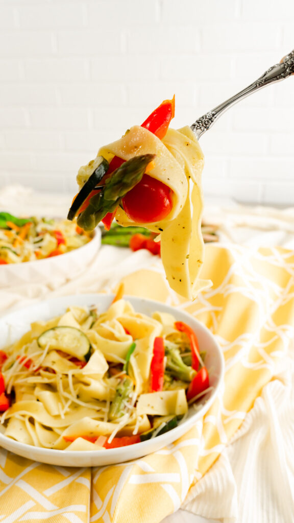 A fork twirled with pappardelle pasta, a piece of asparagus, and cherry tomato lifted above a bowl of pasta primavera.