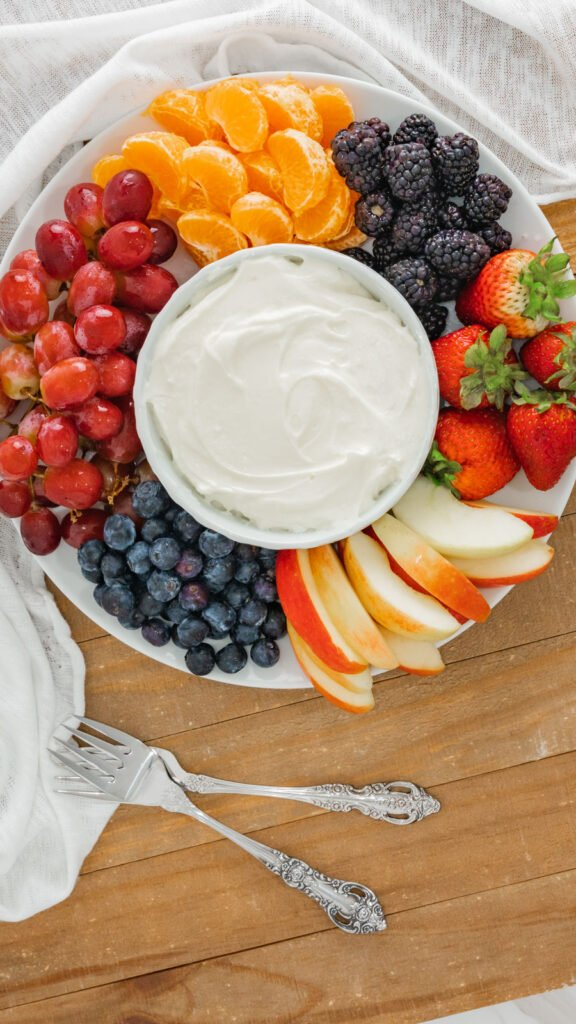 A bowl of fruit dip surrounded by prepared grapes, oranges, blackberries, strawberries, and more.
