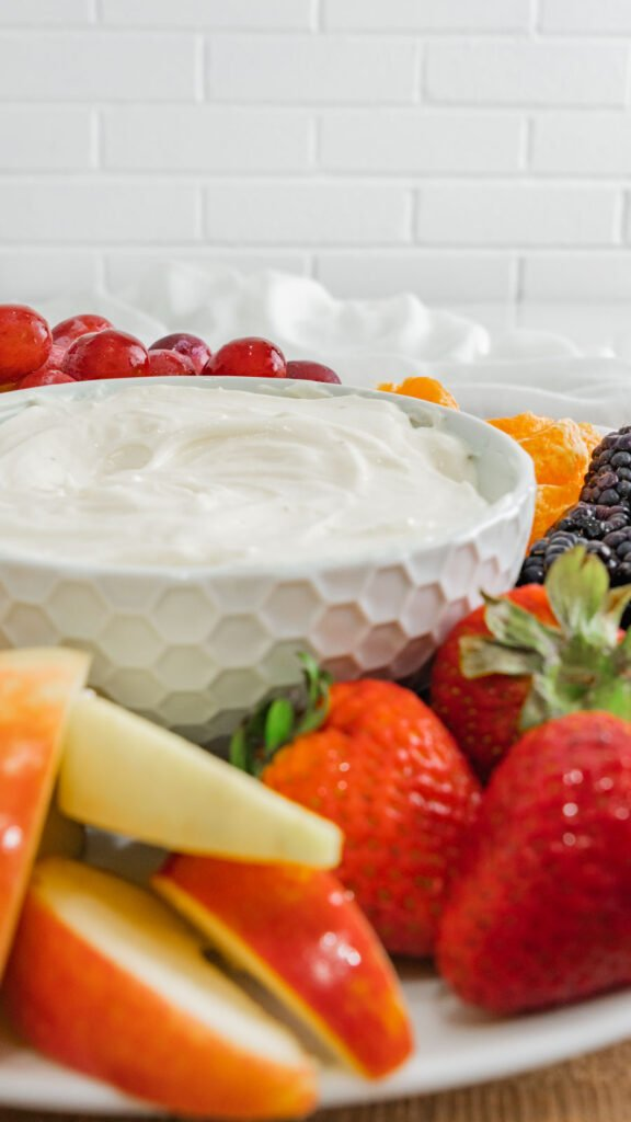 Side view of apple slices and whole strawberries spread around bowl of fruit dip.