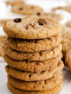 A stack of pecan cookies topped with chocolate chips.
