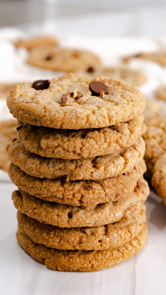 A stack of English toffee pecan cookies topped with toasted pecans and chocolate chips.
