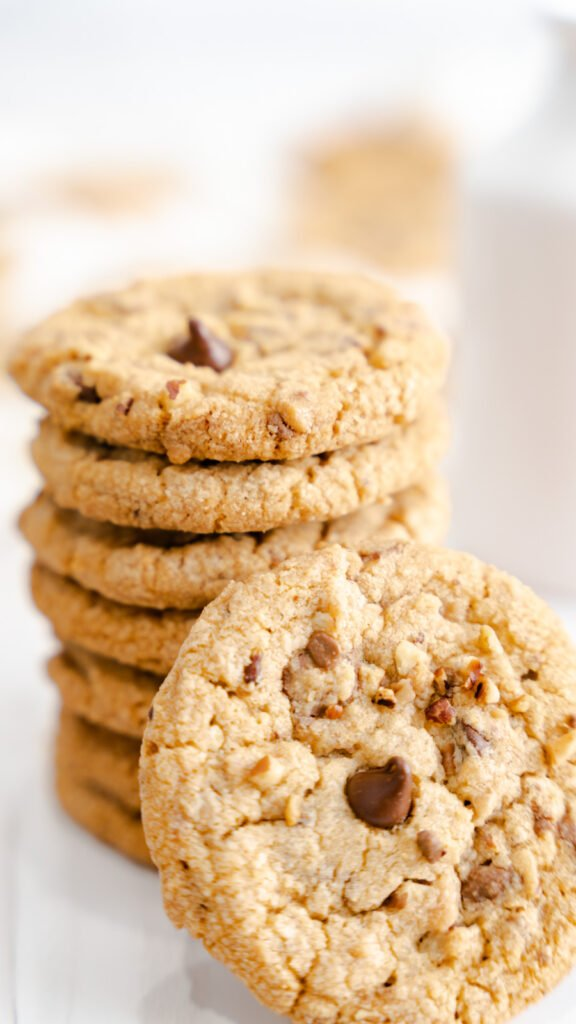 A stack of pecan cookies with one cookie propped in front with chocolate chips and English toffee.