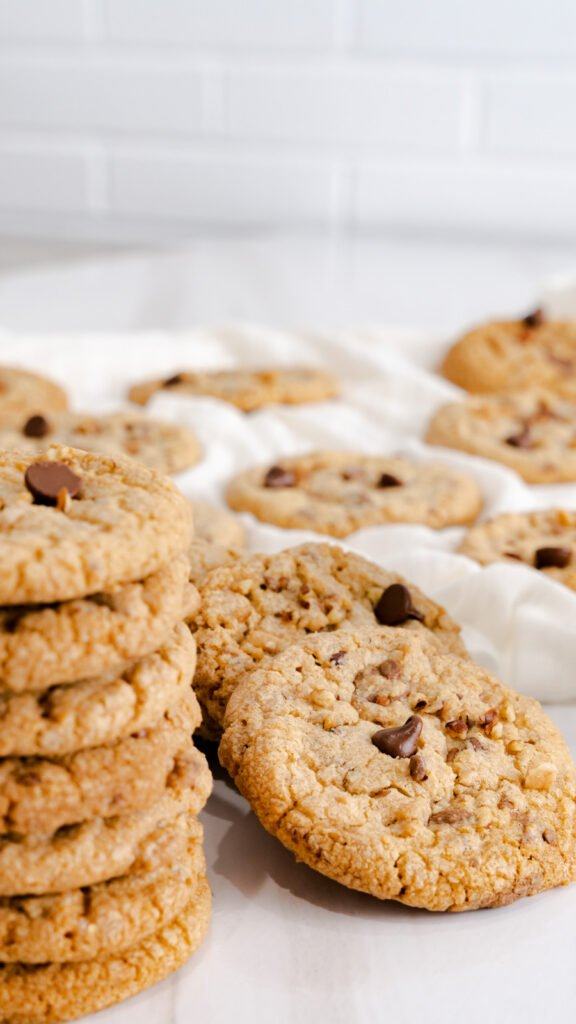 A stack of cookies on the left with a few cookies propped up behind them.