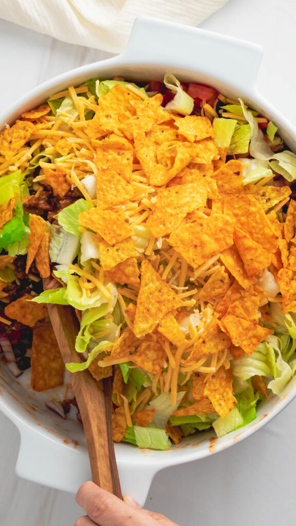 A serving spoon in the casserole dish stirring the taco salad.