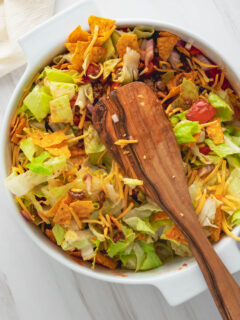 A serving spoon resting on top of a Dorito taco salad in a white casserole dish.