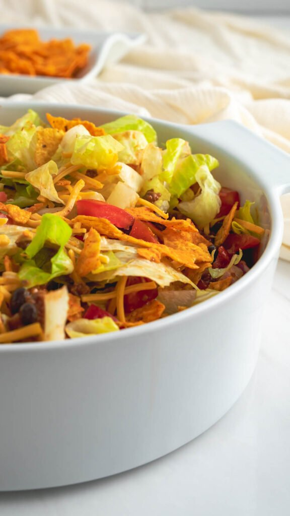 Dorito taco salad served in a white casserole dish topped with fresh romaine lettuce, shredded cheese, and chopped tomatoes.