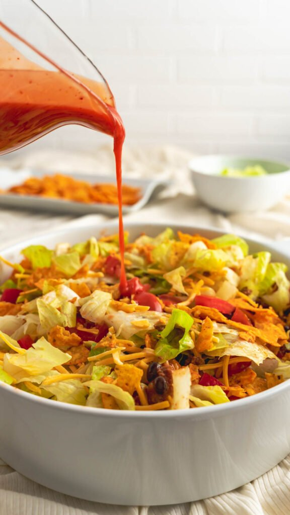 Catalina dressing being drizzled on Dorito taco salad.