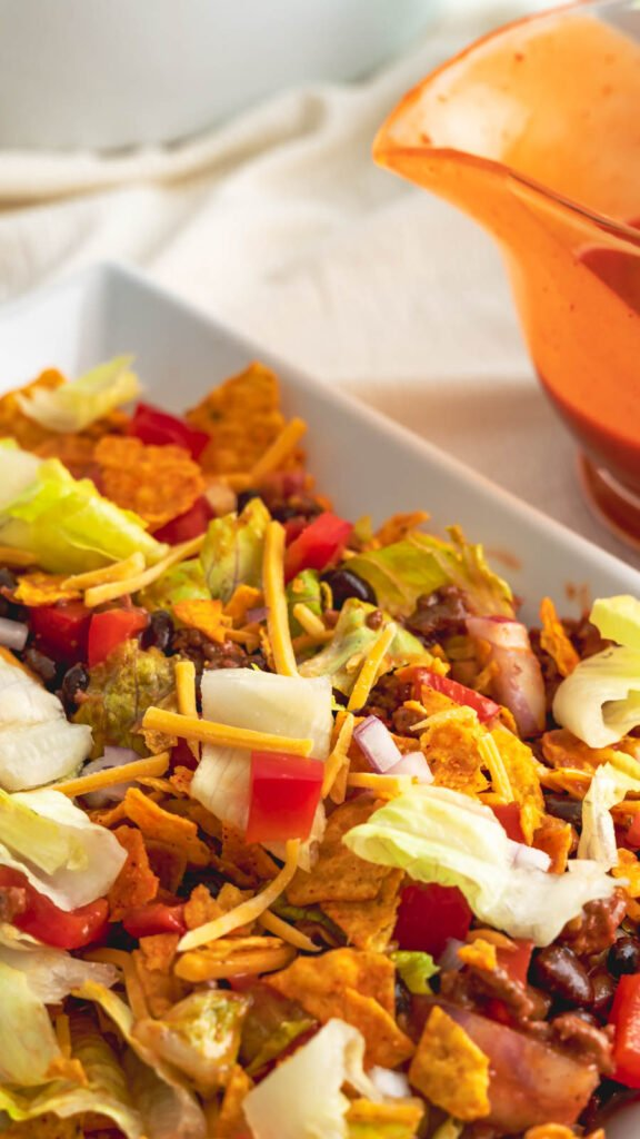 A rectangular plate with Dorito taco salad with chopped lettuce, tomatoes, and shredded cheese.