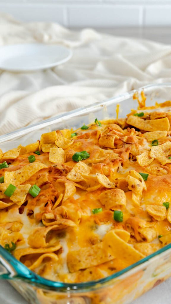 Frito pie in a glass baking dish topped with cheese, scallions, and Fritos.
