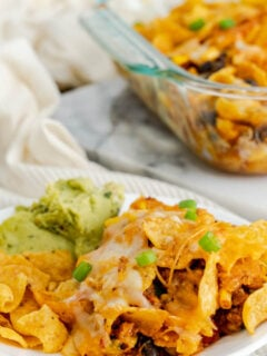 Frito Pie served on a plate with a side of guacamole.