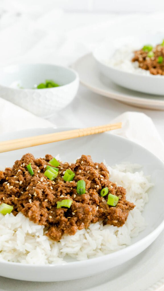 Side view of Korean beef made with ground beef resting on a bed of white rice and served with chopsticks.