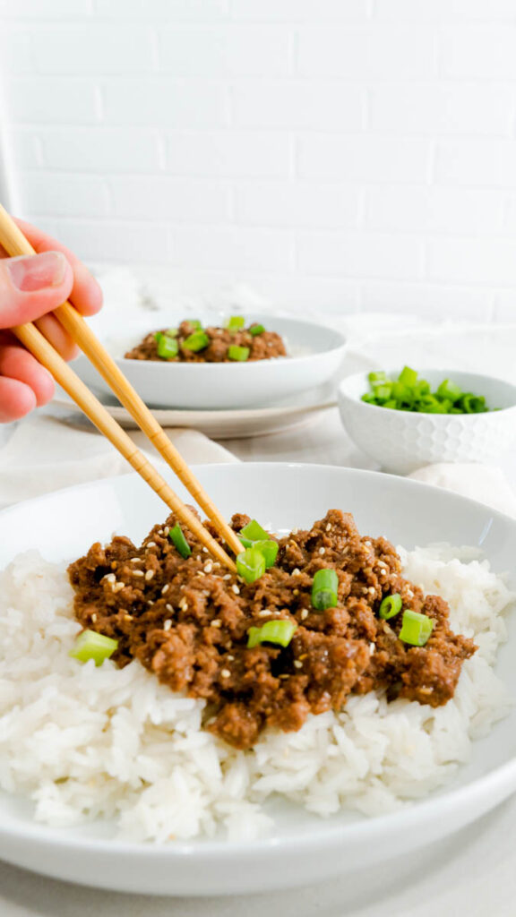 Chopsticks in a bowl of Korean beef on a bed of rice in a white bowl.