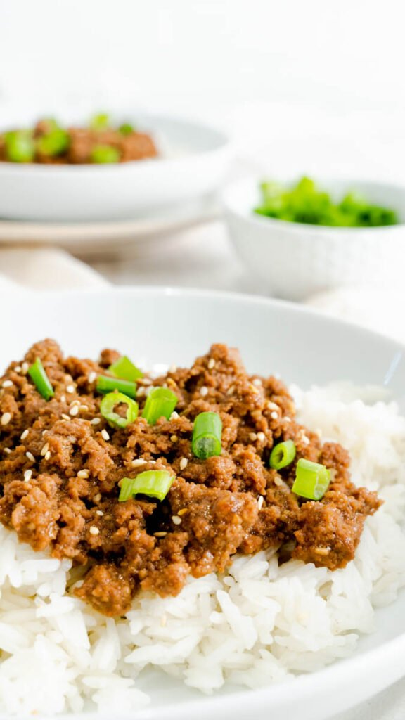 Side view of Instant Pot Korean Beef made with ground beef garnished with scallions and toasted sesame seeds