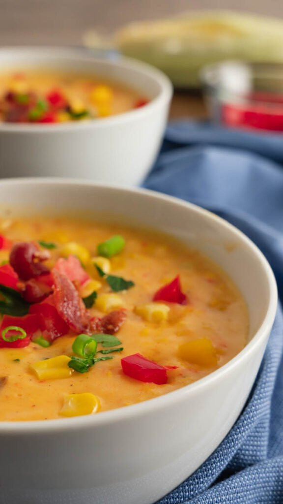 Instant Pot Summer Corn Chowder garnished with fresh tomatoes, parsley, and scallions.