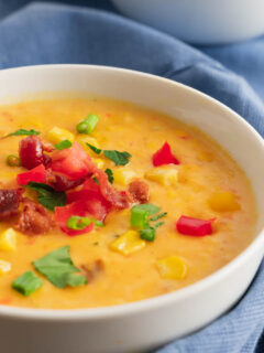 A bowl of corn chowder made with summer vegetables and topped with Roma tomatoes, bacon, and scallions in a while bowl.