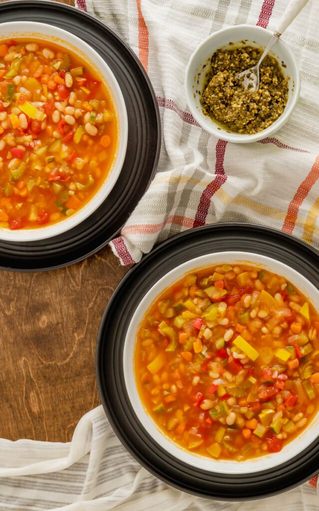 Two bowls of garden vegetable soup with pesto on black charger plates.