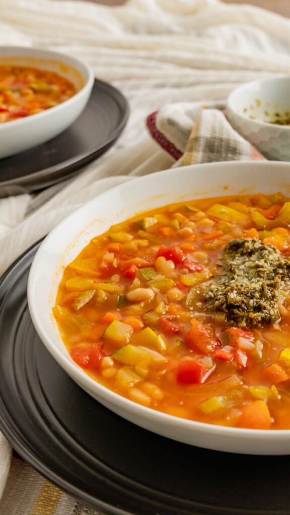 Bowl of pressure cooked vegetable soup with a spoonful of pesto and garnished with parmesan.