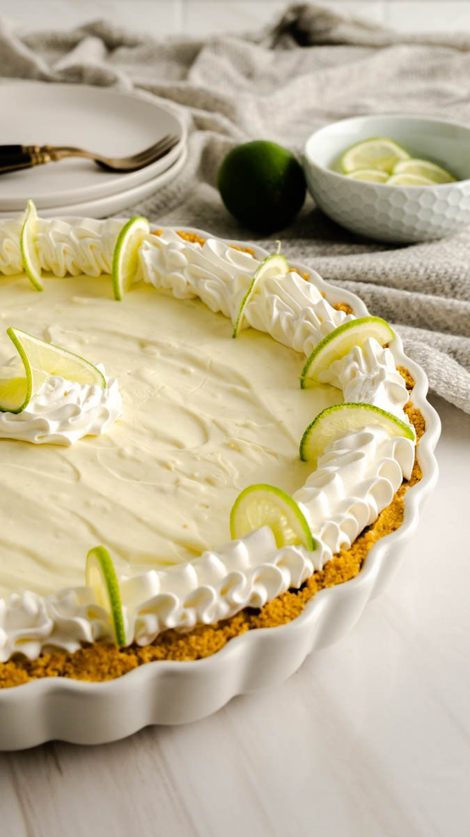 Side view of key lime pie with a graham cracker crust garnished with cool whip and thinly sliced limes.