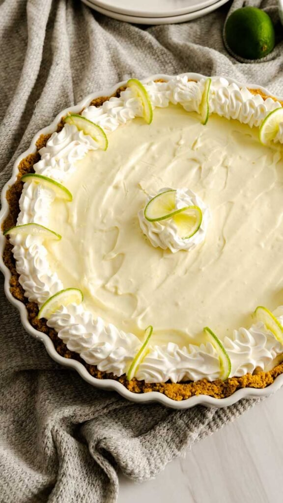 Key lime pie in large pie plate garnished with cool whip and sliced limes.