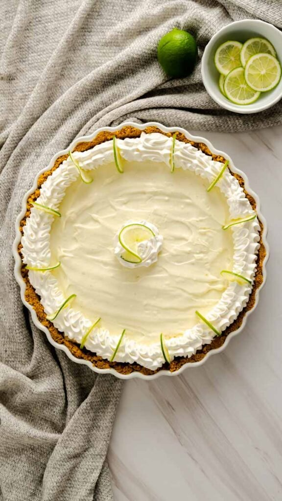 No Bake Key Lime Pie decorated with cool whip and sliced key limes.