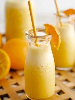 Orange Julius in glass bottle with paper straw and orange wedge.