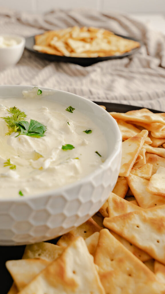 Whipped feta cheese up with chopped parsley, dill, and thyme on black plate with pita chips.