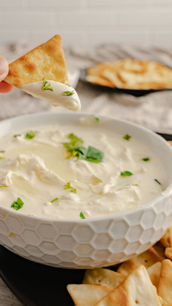 A pita chip lifted above a bowl of freshly made feta cheese dip.