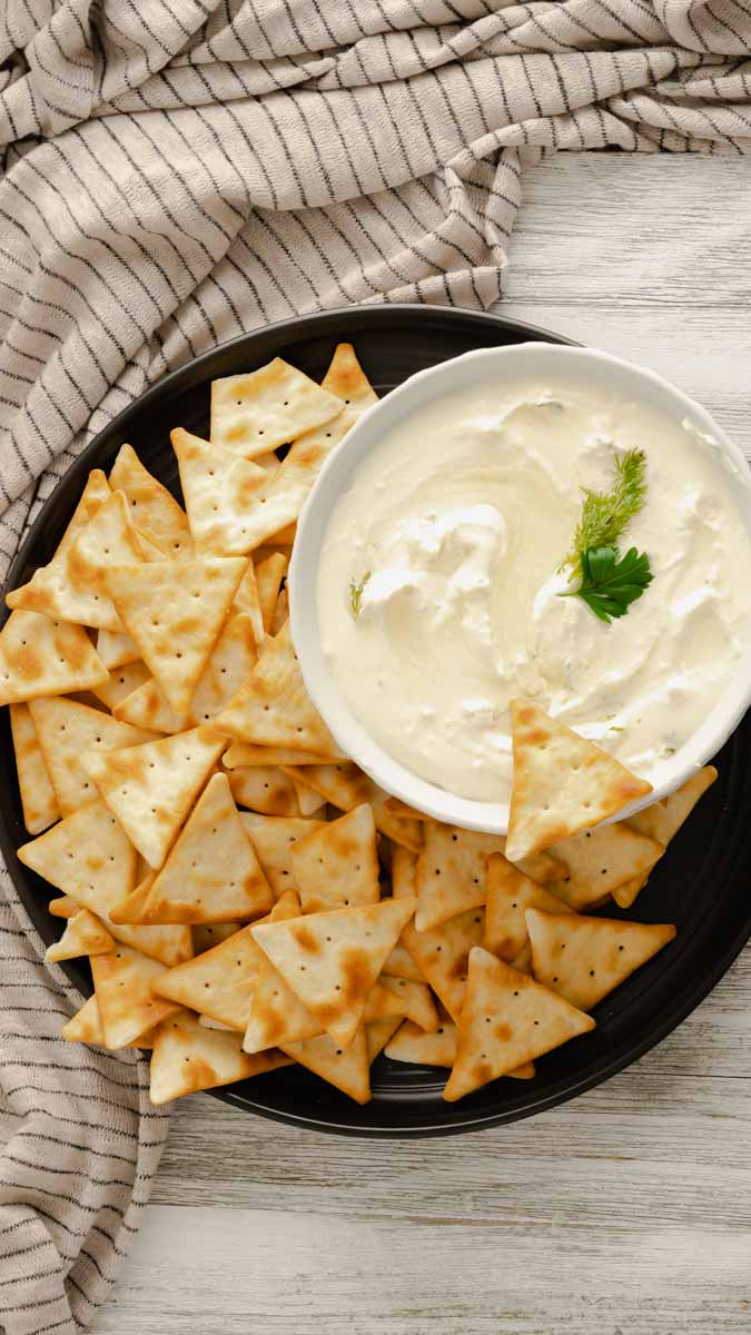 Overhead shot of whipped feta dip in white bowl surrounded by pita chips on black plate.
