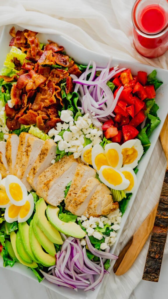 Chicken Cobb salad sitting on a bed of romaine lettuce and topped with jammy eggs, feta cheese, chopped bacon, and tomatoes.