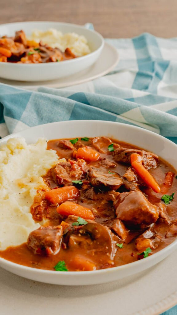 Beef bourguignon with chopped carrots and mushrooms in a red wine sauce served with mashed potatoes.
